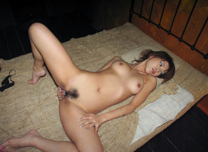 That extremely naughty Asian bitch is laying down on a bed with widely spread legs.jpg