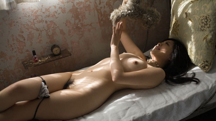 Cute Japanese babe is playing with a teddy bear, while lying down naked on the sofa.jpg